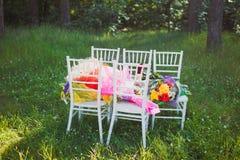 Καρέκλες Chiavari στη χλόη με τα λουλούδια ανθοδεσμών στοκ φωτογραφία με δικαίωμα ελεύθερης χρήσης