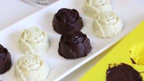 Καραμέλα, που βερνικώνεται στην άσπρη και μαύρη σοκολάτα Γεμισμένος με τα τεμαχισμένα αμύγδαλα Σε ένα άσπρο πιάτο Κοντά στη μορφή φιλμ μικρού μήκους