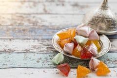 Καραμέλες ζάχαρης Akide στο παλαιό μεταλλικό πιάτο στον εκλεκτής ποιότητας πίνακα Στοκ Εικόνες