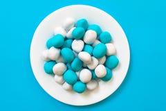Καραμέλες - μπισκότα του άσπρου και μπλε χρώματος υπό μορφή πέτρας θάλασσας σε ένα άσπρο πιάτο σε ένα μπλε υπόβαθρο στοκ φωτογραφία με δικαίωμα ελεύθερης χρήσης