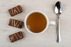 Καραμέλες σοκολάτας, φλυτζάνι του τσαγιού και κουταλάκι του γλυκού στον ξύλινο πίνακα Στοκ Εικόνες