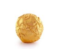 Καραμέλα γλυκιάς σοκολάτας που τυλίγεται στο χρυσό φύλλο αλουμινίου Στοκ Φωτογραφία