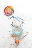 Καραμέλα - η ζωηρόχρωμη ζάχαρη ψεκάζει και ένα lollipop Στοκ Φωτογραφία