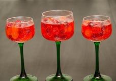 Καραμέλα και γεμισμένα χυμός γυαλιά κρασιού στο τρίο Στοκ Φωτογραφία
