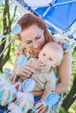 Καραμέλα-πίνακας Το αγοράκι τρώει το κέικ γενεθλίων με τα χέρια Η μητέρα του τον παίρνει Γιορτή γενεθλίων στο πάρκο στο πικ-νίκ Στοκ εικόνα με δικαίωμα ελεύθερης χρήσης