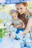 Καραμέλα-πίνακας Το αγοράκι τρώει το κέικ γενεθλίων με τα χέρια Η μητέρα του τον παίρνει Γιορτή γενεθλίων στο πάρκο στο πικ-νίκ Στοκ Εικόνα