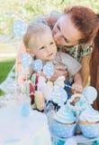Καραμέλα-πίνακας Το αγοράκι τρώει το κέικ γενεθλίων με τα χέρια Η μητέρα του τον παίρνει Γιορτή γενεθλίων στο πάρκο στο πικ-νίκ Στοκ Φωτογραφία