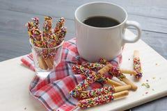 Καραμέλα Pepero με τον καυτό καφέ στο ξύλινο υπόβαθρο Στοκ Φωτογραφίες