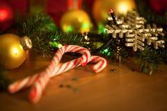 Καραμέλες Χριστουγέννων με τη γιρλάντα και τα μπιχλιμπίδια Στοκ Φωτογραφίες