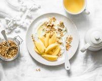 Καραμελοποιημένο κυδώνι με το ελληνικά γιαούρτι, το granola και τα καρύδια σε ένα ελαφρύ υπόβαθρο, τοπ άποψη εύγευστος υγιής προγ στοκ φωτογραφίες