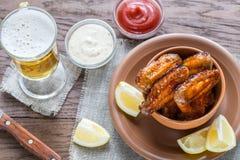 Καραμελοποιημένα φτερά κοτόπουλου με το ποτήρι της μπύρας Στοκ Εικόνες