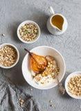 Καραμελοποιημένα ψημένα αχλάδια με το ελληνικά γιαούρτι και το granola σε ένα γκρίζο υπόβαθρο, τοπ άποψη στοκ εικόνες με δικαίωμα ελεύθερης χρήσης