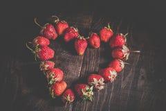 Καρδιά από μια φράουλα σε ένα ξύλινο υπόβαθρο Στοκ Φωτογραφίες