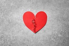 Καρδιά εγγράφου που κόβεται στο μισό και που συρράπτεται πίσω στοκ εικόνα