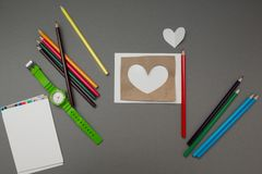 Καρδιά εγγράφου που περιβάλλεται με τις σχολικές προμήθειες στοκ φωτογραφία