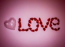 Καρδιά και αγάπη λέξης που σχεδιάζεται από τα τεχνητά λουλούδια σε ένα ρόδινο υπόβαθρο στοκ φωτογραφία