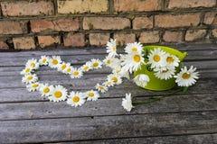 Καρδιά και ανθοδέσμη των chamomile λουλουδιών σε μια ξύλινη επιφάνεια Στοκ Φωτογραφίες