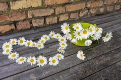 Καρδιά και ανθοδέσμη των chamomile λουλουδιών σε μια ξύλινη επιφάνεια Στοκ Φωτογραφία