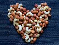 Καρδιά καρυδιών στο σκοτεινό υπόβαθρο Αμύγδαλο, το δυτικό ανακάρδιο, καρύδια φουντουκιών Αγροτικό πρότυπο εμβλημάτων οργανικής τρ Στοκ Εικόνα