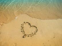 Καρδιά που επισύρεται την προσοχή στην άμμο με το θαλάσσιο νερό κοντά σε το Στοκ Εικόνα