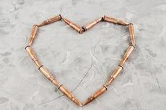 Καρδιά που σχεδιάζεται των σφαιρών μετάλλων για το επιθετικό τουφέκι σπασμένο στο γκρι σκυρόδεμα Στοκ εικόνες με δικαίωμα ελεύθερης χρήσης