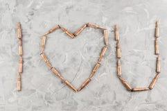 Καρδιά που σχεδιάζεται των σφαιρών μετάλλων για το επιθετικό τουφέκι σπασμένο στο γκρι σκυρόδεμα Στοκ Φωτογραφία