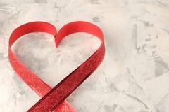 Καρδιά της κόκκινης κορδέλλας σε ένα ελαφρύ συγκεκριμένο υπόβαθρο βαλεντίνος ημέρας s Διάστημα για το κείμενο στοκ εικόνα με δικαίωμα ελεύθερης χρήσης