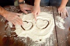 Καρδιά του αλευριού στο ξύλινο γραφείο που χρωματίζεται από ένα ζεύγος Στοκ φωτογραφία με δικαίωμα ελεύθερης χρήσης