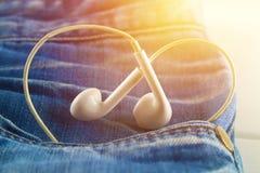 Καρδιά των άσπρων ακουστικών - ένα σύμβολο της αγάπης τιτιβίζει από την τσέπη του παντελονιού τζιν Αγάπη για τη μουσική Η έννοια  Στοκ εικόνα με δικαίωμα ελεύθερης χρήσης