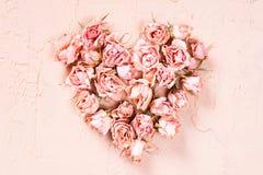 Καρδιά των ξηρών ρόδινων τριαντάφυλλων στο κατασκευασμένο υπόβαθρο Στοκ Εικόνα