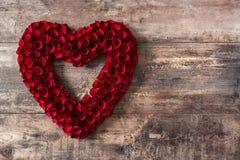Καρδιά φιαγμένη από κόκκινα τριαντάφυλλα στον ξύλινο πίνακα στοκ εικόνες