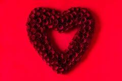 Καρδιά φιαγμένη από κόκκινα τριαντάφυλλα στο κόκκινο υπόβαθρο στοκ εικόνα