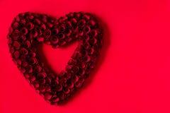 Καρδιά φιαγμένη από κόκκινα τριαντάφυλλα στο κόκκινο υπόβαθρο στοκ φωτογραφίες με δικαίωμα ελεύθερης χρήσης