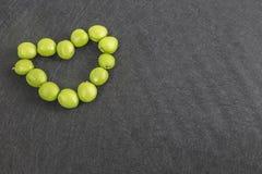 Καρδιά, φιαγμένη από πράσινα βερίκοκα στο υπόβαθρο Με το διάστημα αντιγράφων στοκ εικόνες με δικαίωμα ελεύθερης χρήσης
