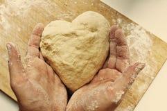 καρδιά χεριών που κρατά τη σπιτική ζύμη ατόμων διαμορφωμένη Στοκ Φωτογραφίες