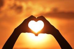 Καρδιά χεριών σκιαγραφιών στην ανατολή και το ηλιοβασίλεμα στοκ εικόνα
