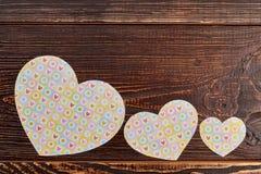 Καρδιές εγγράφου στο καφετί ξύλινο υπόβαθρο Στοκ Εικόνες
