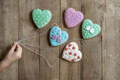 καρδιές μελοψωμάτων εκμετάλλευσης χεριών παιδιού για τις σειρές όπως τα μπαλόνια στοκ φωτογραφία με δικαίωμα ελεύθερης χρήσης