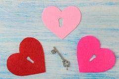 Καρδιές με μια κλειδαρότρυπα και ένα κλειδί στο μπλε ξύλινο υπόβαθρο επάνω από την όψη βαλεντίνος ημέρας s στοκ φωτογραφίες με δικαίωμα ελεύθερης χρήσης