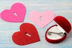 Καρδιές με μια κλειδαρότρυπα και ένα κλειδί στο μπλε ξύλινο υπόβαθρο βαλεντίνος ημέρας s στοκ φωτογραφία με δικαίωμα ελεύθερης χρήσης
