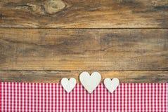 Καρδιές με το κόκκινο ελεγμένο ύφασμα στο καφετί ξύλο Στοκ Εικόνες