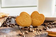 Καρδιές μπισκότων με την αγάπη λέξης στο υπόβαθρο φασολιών Στοκ Εικόνα