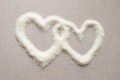 Καρδιές, που χύνονται άσπρες με τη ζάχαρη γλυκό ζευγών Σε ένα ουδέτερο υπόβαθρο Στοκ φωτογραφία με δικαίωμα ελεύθερης χρήσης
