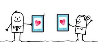 Καρδιές προσοχής ζεύγους κινούμενων σχεδίων στις ταμπλέτες Στοκ Φωτογραφίες