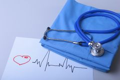 Καρδιογράφημα με το ιατρικό παλτό στηθοσκοπίων και γιατρών στον πίνακα Στοκ Εικόνες