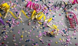Καρναβάλι ή γιορτή γενεθλίων, κομφετί και serpentines στο γκρίζο υπόβαθρο στοκ φωτογραφίες