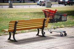 Καροτσάκι αγορών δίπλα στον πάγκο πάρκων Στοκ φωτογραφίες με δικαίωμα ελεύθερης χρήσης