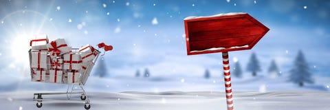 Καροτσάκι αγορών με τα δώρα και ξύλινο σημάδι στο χειμερινό τοπίο Χριστουγέννων Στοκ Εικόνα
