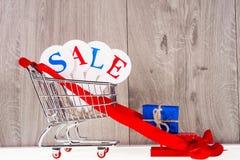 Καροτσάκι αγορών με τα κιβώτια δώρων σε ένα ξύλινο υπόβαθρο Πώληση διακοπών Στοκ Φωτογραφίες