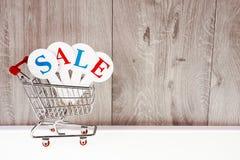 Καροτσάκι αγορών με τα κιβώτια δώρων σε ένα ξύλινο υπόβαθρο Πώληση διακοπών Στοκ εικόνα με δικαίωμα ελεύθερης χρήσης